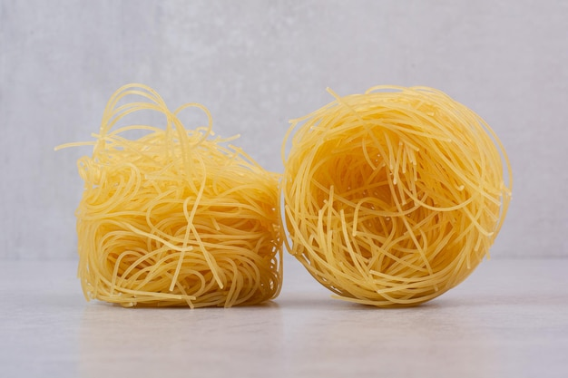 Uncooked spaghetti nests on marble table.