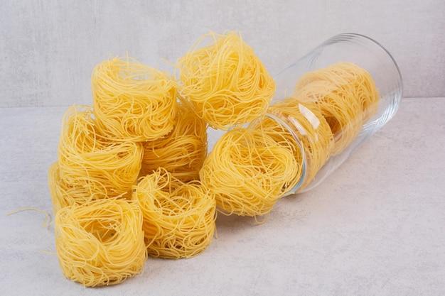 Сырые спагетти гнездятся на мраморном столе с флягой.