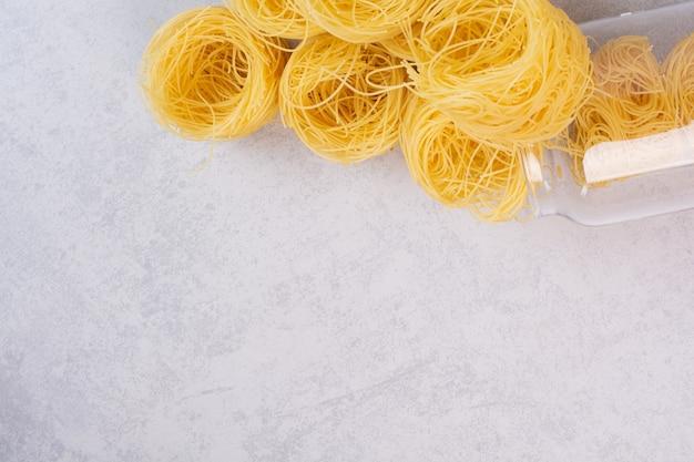 Nidi di spaghetti crudi sulla superficie di pietra con vaso di vetro