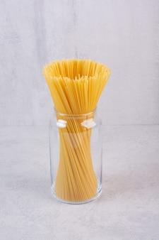Сырые макароны спагетти в стеклянной банке