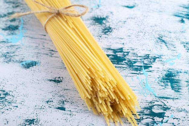 Сырые макароны спагетти, перевязанные веревкой на красочной поверхности.