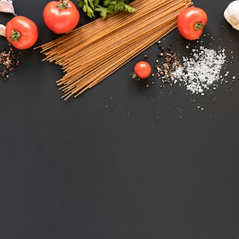 Uncooked spaghetti pasta; tomatoes; garlic and black pepper over black surface
