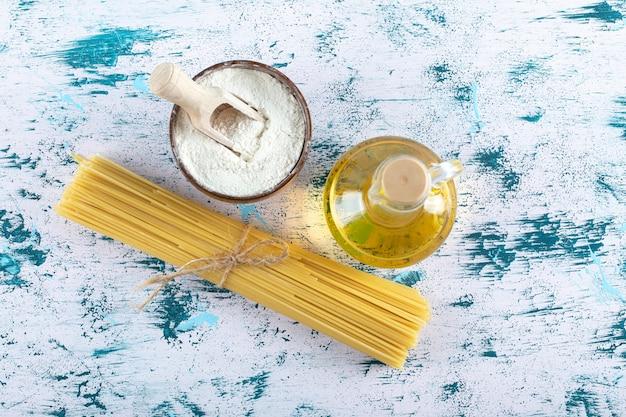 白い背景の上の小麦粉とオイルボトルと未調理のスパゲッティパスタ。高品質の写真