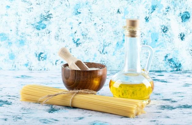 白地に小麦粉とオイルボトルを添えた未調理のスパゲッティパスタ。