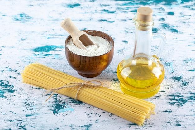 Pasta cruda degli spaghetti con farina e bottiglia di olio su bianco.