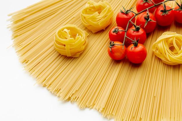 Сырые спагетти тальятелле и помидоры
