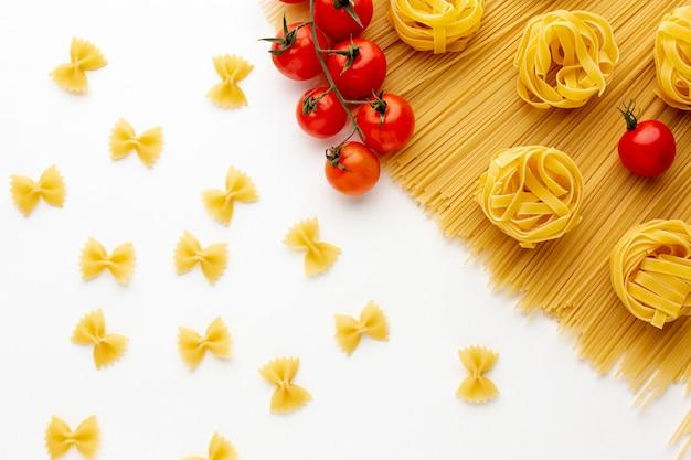 Uncooked spaghetti tagliatelle farfalle and tomatoes