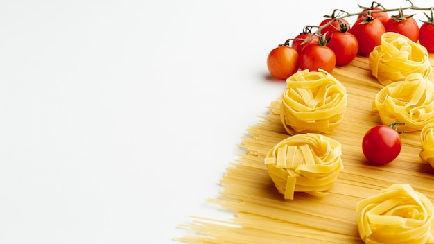 Uncooked spaghetti tagliatelle and tomatoes with copy space