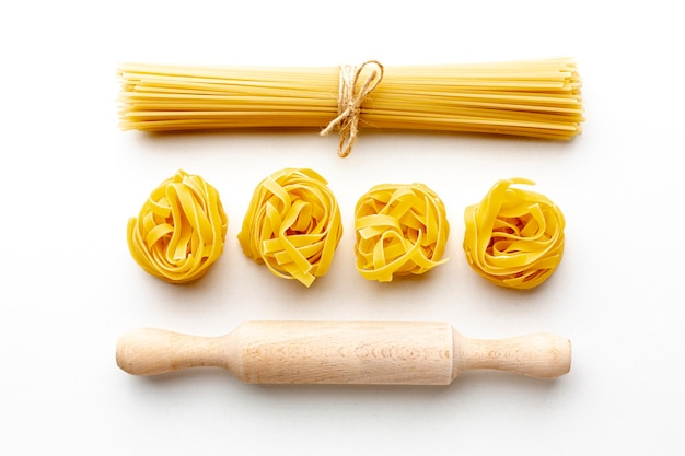 Uncooked spaghetti and tagliatelle with rolling pin