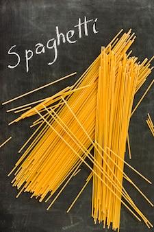 Uncooked spaghetti and text written on blackboard