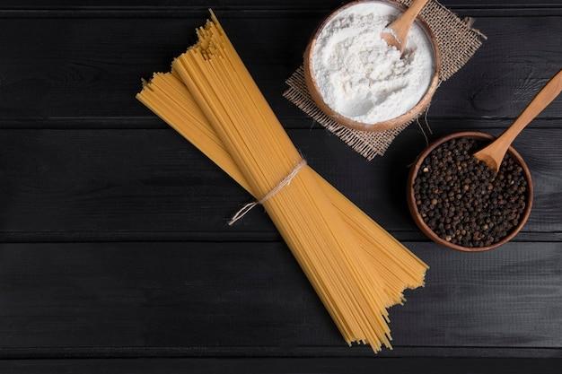 나무 테이블 위에 놓인 밧줄과 후추로 묶인 요리하지 않은 스파게티. 고품질 사진