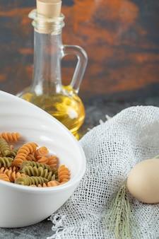Maccheroni a spirale crudi nel piatto bianco con l'uovo e la bottiglia di olio
