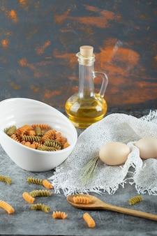 Maccheroni a spirale crudi nel piatto bianco con le uova e la bottiglia di olio