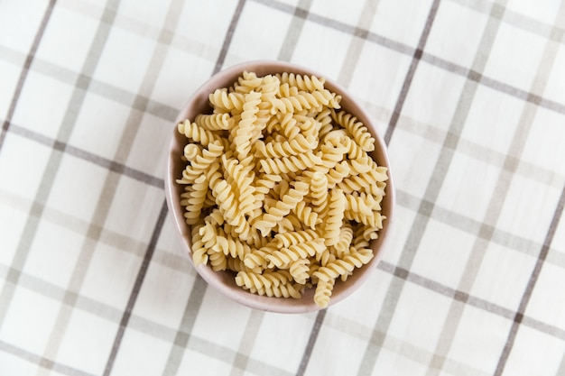 Uncooked spiral pasta in the ceramic plate. plaid tablecloth wall. top view