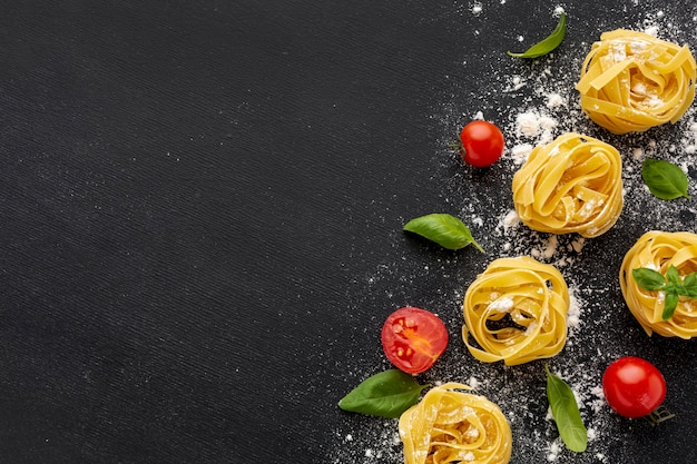 Uncooked tagliatelle on black background with tomatoes basil with copy space