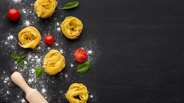 Uncooked tagliatelle on black background with tomatoes rolling pin and copy space
