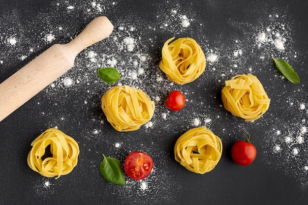 Uncooked tagliatelle on black background with tomatoes and rolling pin