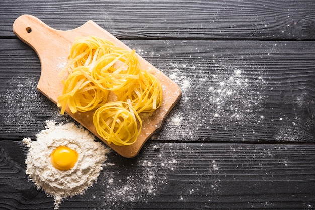 Uncooked tagliatelle on chopping board with egg york in flour on wooden plank