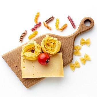 Uncooked tagliatelle farfalle fusilli with hard cheese and tomato