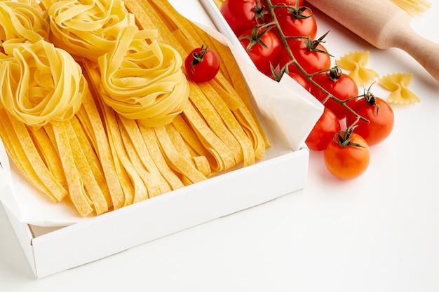 Uncooked tagliatelle fettuccine and tomatoes