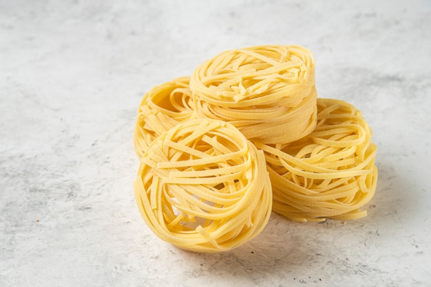 Uncooked tagliatelle pasta nests on white background.