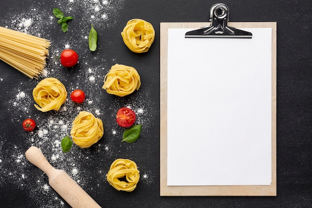 Uncooked tagliatelle spaghetti on black background with tomatoes rolling pin and clipboard mock-up