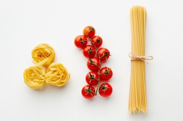 Uncooked tagliatelle spaghetti and cherry tomatoes
