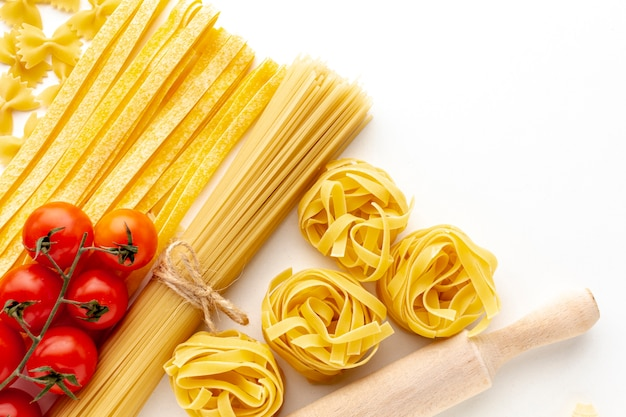 Сырые тальятелле, спагетти, феттучини и помидоры