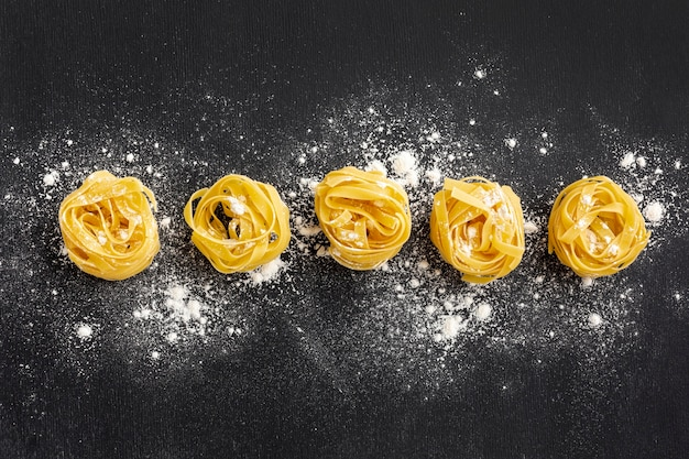 Uncooked tagliatelle with flour on black background