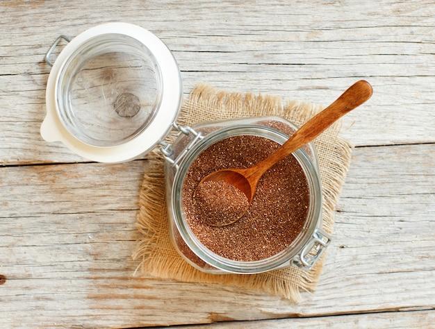 スプーンの上面図が付いているガラス瓶の未調理のテフ穀物