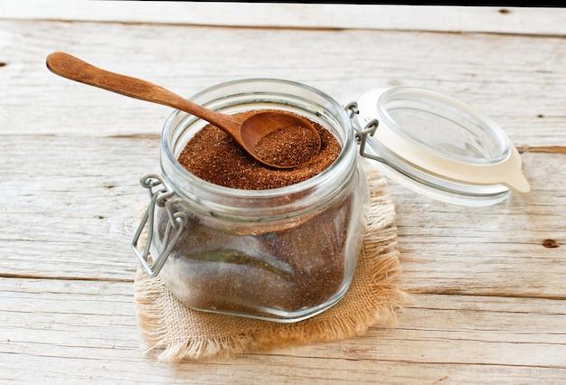 スプーンでガラスの瓶に未調理のテフ穀物