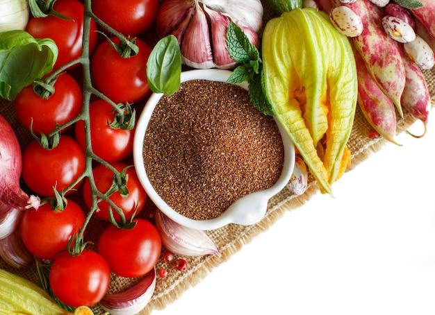 白い境界線で分離された野菜と未調理のテフ穀物