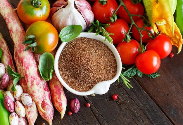 木の上に野菜と未調理のテフ穀物