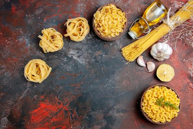 Сырые три спагетти и макароны с бабочкой в коричневой миске и бутылка с зеленым луком, лимоном и чесноком на смешанном цветном фоне