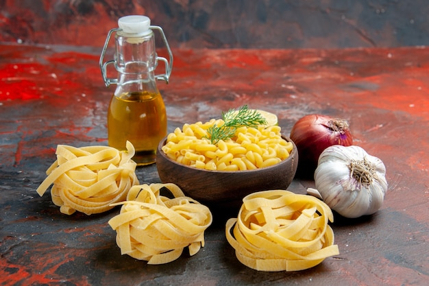 Uncooked three spaghetti and butterfly pastas in a brown bowl and green onion lemon garlic oil bottle on mixed color background