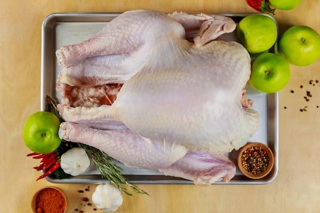 木製の表面に食材とスパイスを使った未調理の七面鳥。