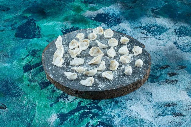 Uncooked turkish ravioli on board on blue.