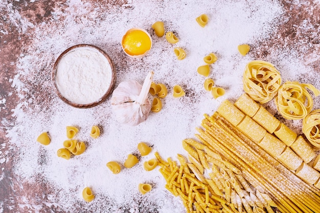 Uncooked various pasta with flour on wooden table.