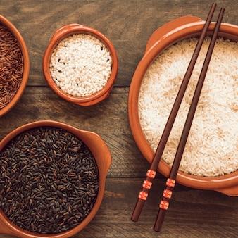 생 쌀된 백미; 나무 테이블에 검은 쌀과 재 스민 빨간 밥 그릇