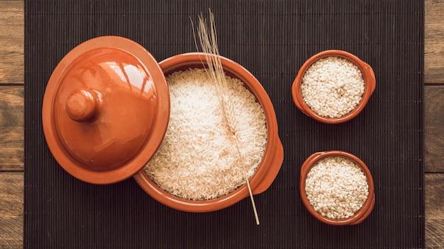 Grani di riso bianco crudo sulla pentola e due ciotole su tovaglietta