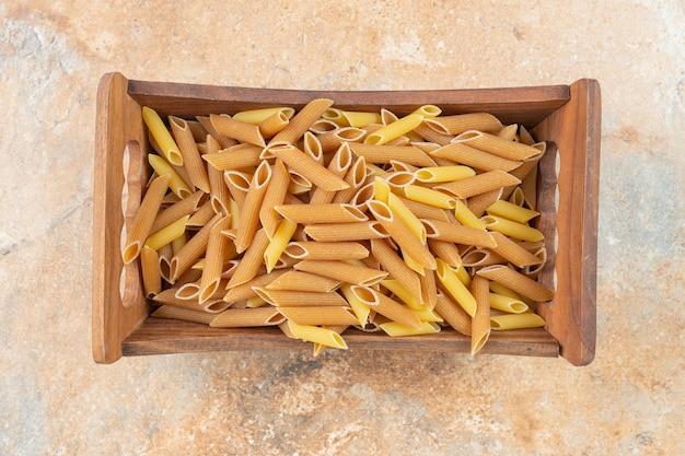 Uncooked whole grain penne pasta in a wooden box on the marble surface