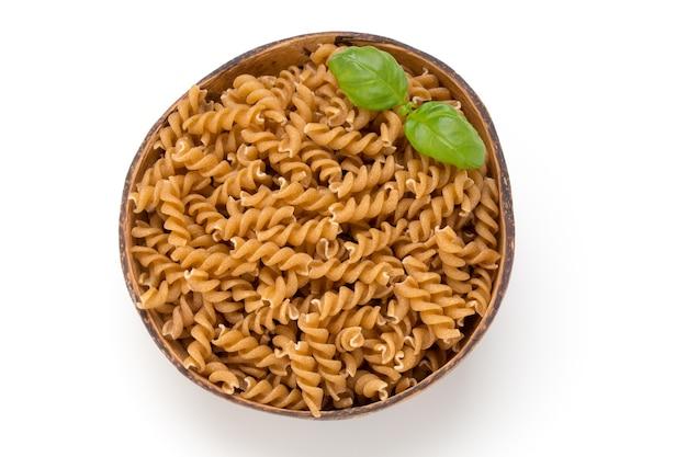 Сырые макароны из цельной еды, изолированные на белом фоне