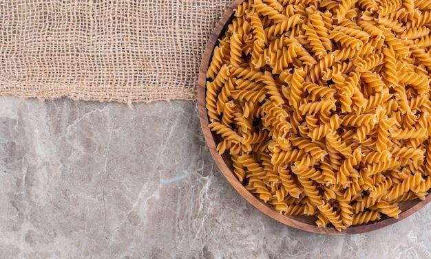 大理石の表面の黄麻布の上の木の板の上の未調理の全粒小麦のフジッリ