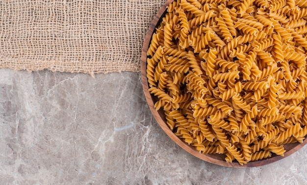 Uncooked whole wheat fusilli on a wooden plate on a burlap on the marble surface Premium Photo