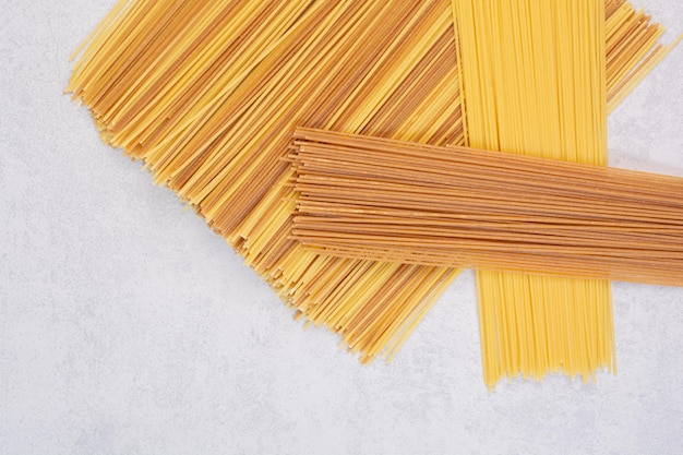Uncooked yellow and brown spaghetti on marble table.