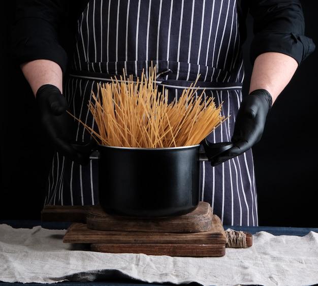 黒い金属鍋に調理されていない黄色の長いスパゲッティと縞模様のエプロンのシェフ