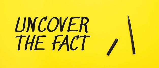 黄色の背景に黒のマーカーで事実のサインを見つけてください。テキスト用のコピースペースが用意されています。