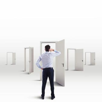 Нерешительный бизнесмен в выборе правильной двери, ведущей к успеху