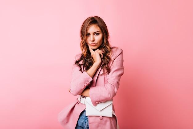 ピンクのジャケットが立っている未定の生姜の女性。暗いウェーブのかかった髪のかわいい白人の女の子の屋内ショット。