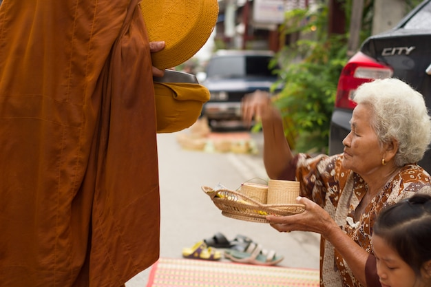 Undefined people are preparing food for alms to buddhist monks in walkway